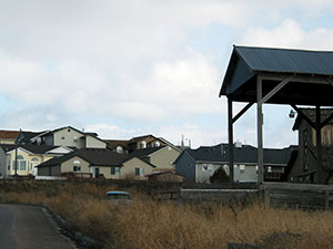 Rustic barn roof in foreground, modern residences in background